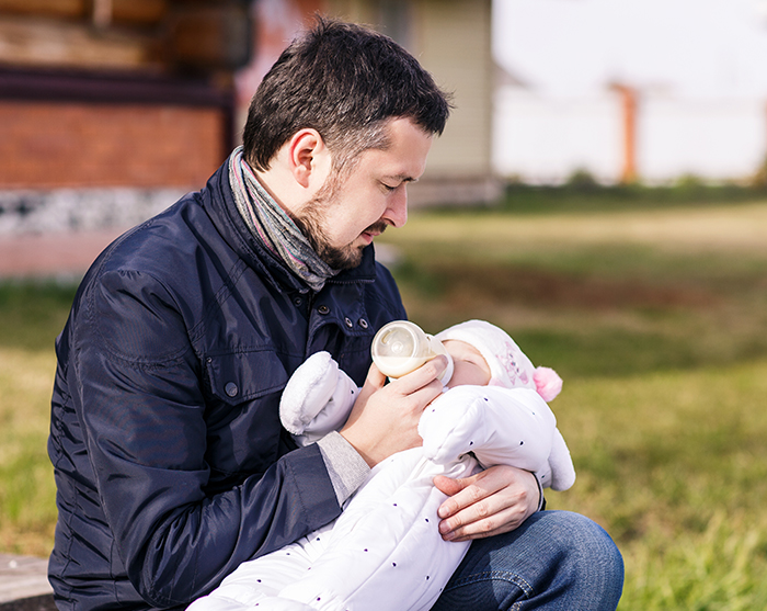 Portrait of father feeding newborn baby outdoor